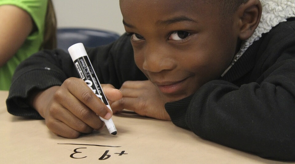 Boy drawing maths on the table